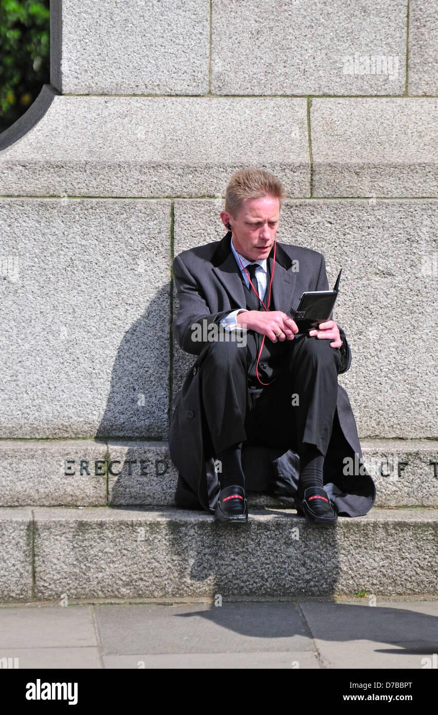 Londres, Angleterre, Royaume-Uni. Homme en costume en train de lire un livre électronique Banque D'Images