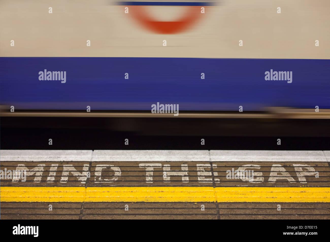 La station de métro Bank 'Mind l'écart' signe peint sur la plate-forme de station avec fast Photo Stock