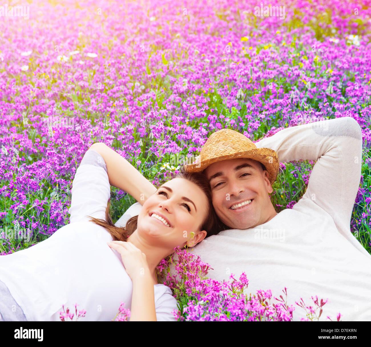 Beau couple heureux couché sur champ de lavande pourpre, s'amusant sur glade floral d'été, Photo Stock