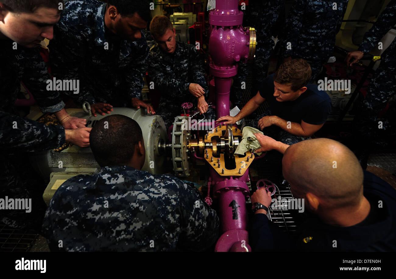 Les marins effectuer la maintenance d'un pompe de service. Photo Stock