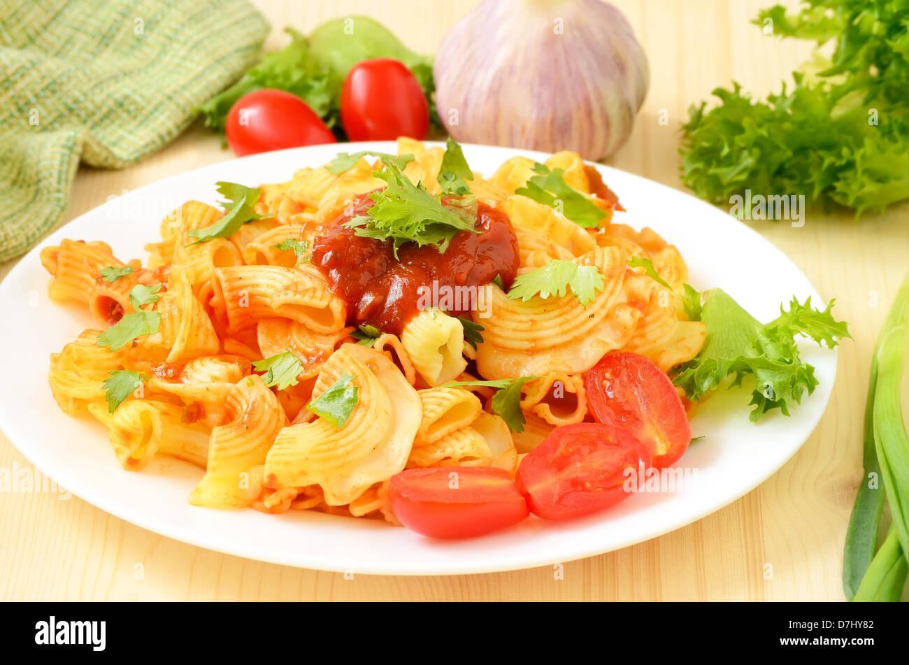 Des pâtes avec sauce tomate sur plaque blanche sur la table en bois Banque D'Images