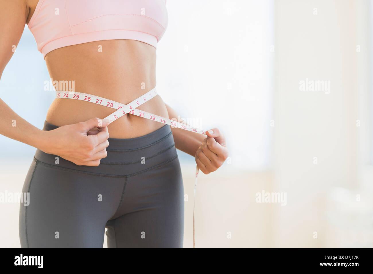 Woman measuring waist Photo Stock
