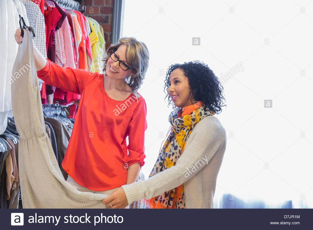 Femme propriétaire de petite entreprise assisting customer avec choix de vêtements Photo Stock