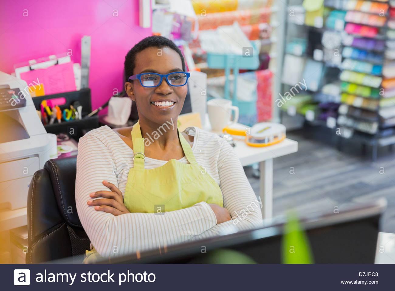 Femme propriétaire de petite entreprise en magasin relaxant Photo Stock