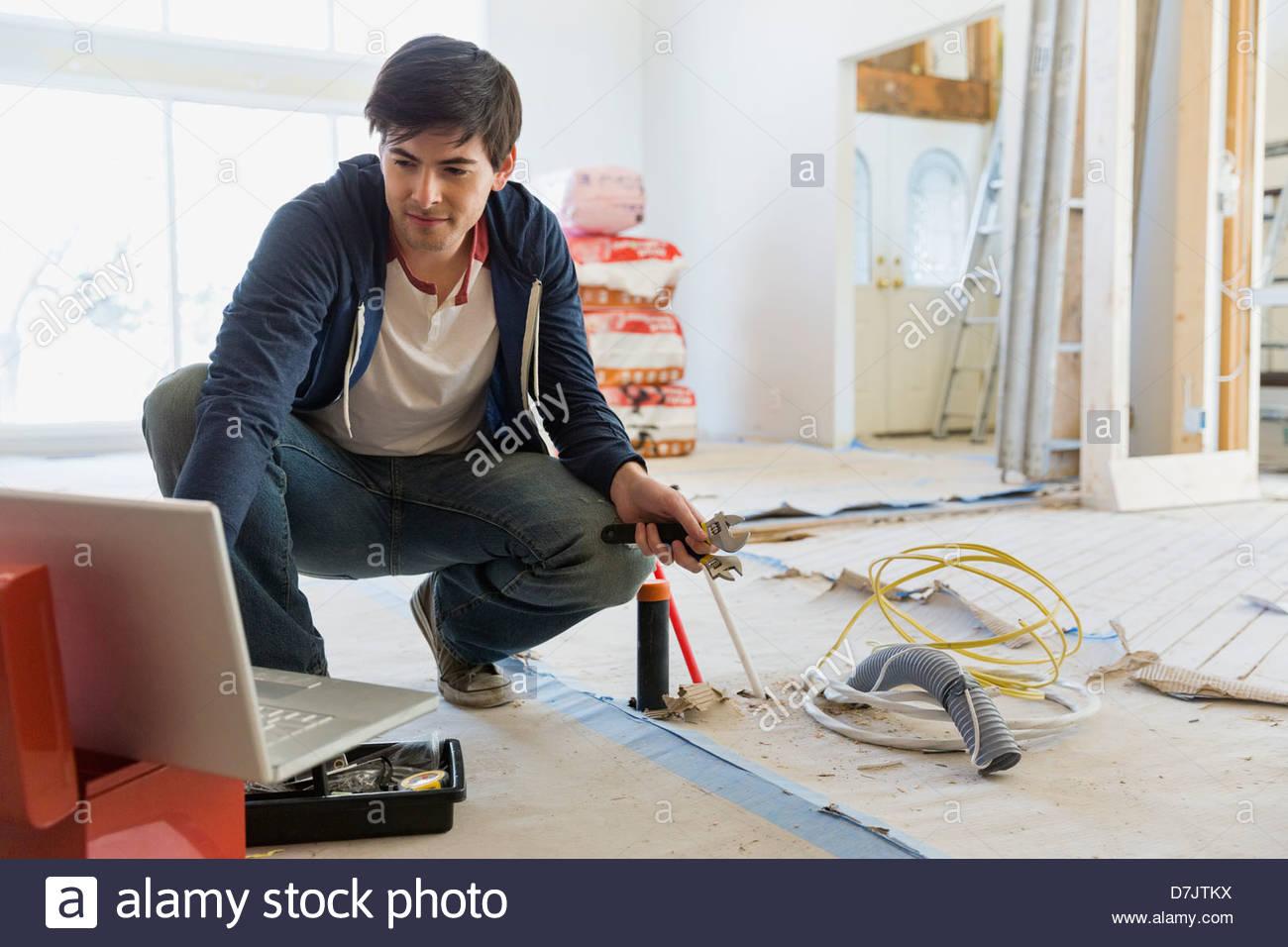Jeune homme consulting conseils en ligne pour des rénovations Photo Stock