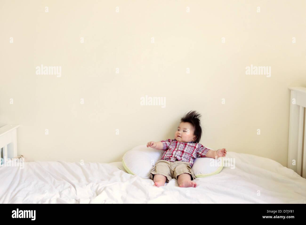 Enfant coréen-américain avec les cheveux noirs hérissés de détente sur double bras tendus Photo Stock