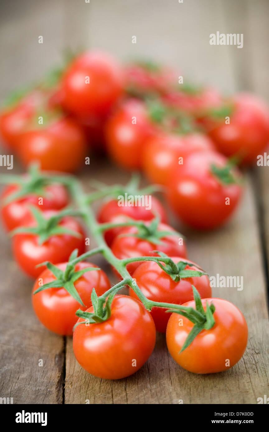 Close up d'une chaîne de vigne, tomates cerise mûre sur une table en bois rustique. Photo Stock