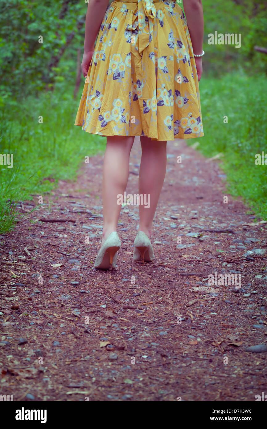 Les jambes d'une femme dans une robe jaune marche sur un sentier dans les bois Photo Stock