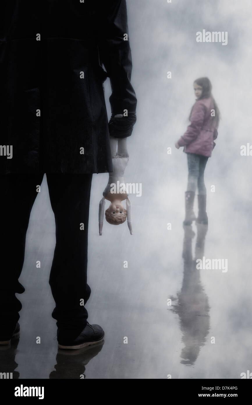 Un homme sombre avec une vieille poupée menace une jeune fille Photo Stock