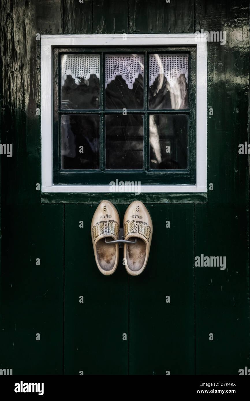 Dutch des chaussures en bois suspendu à une porte verte avec une fenêtre Photo Stock