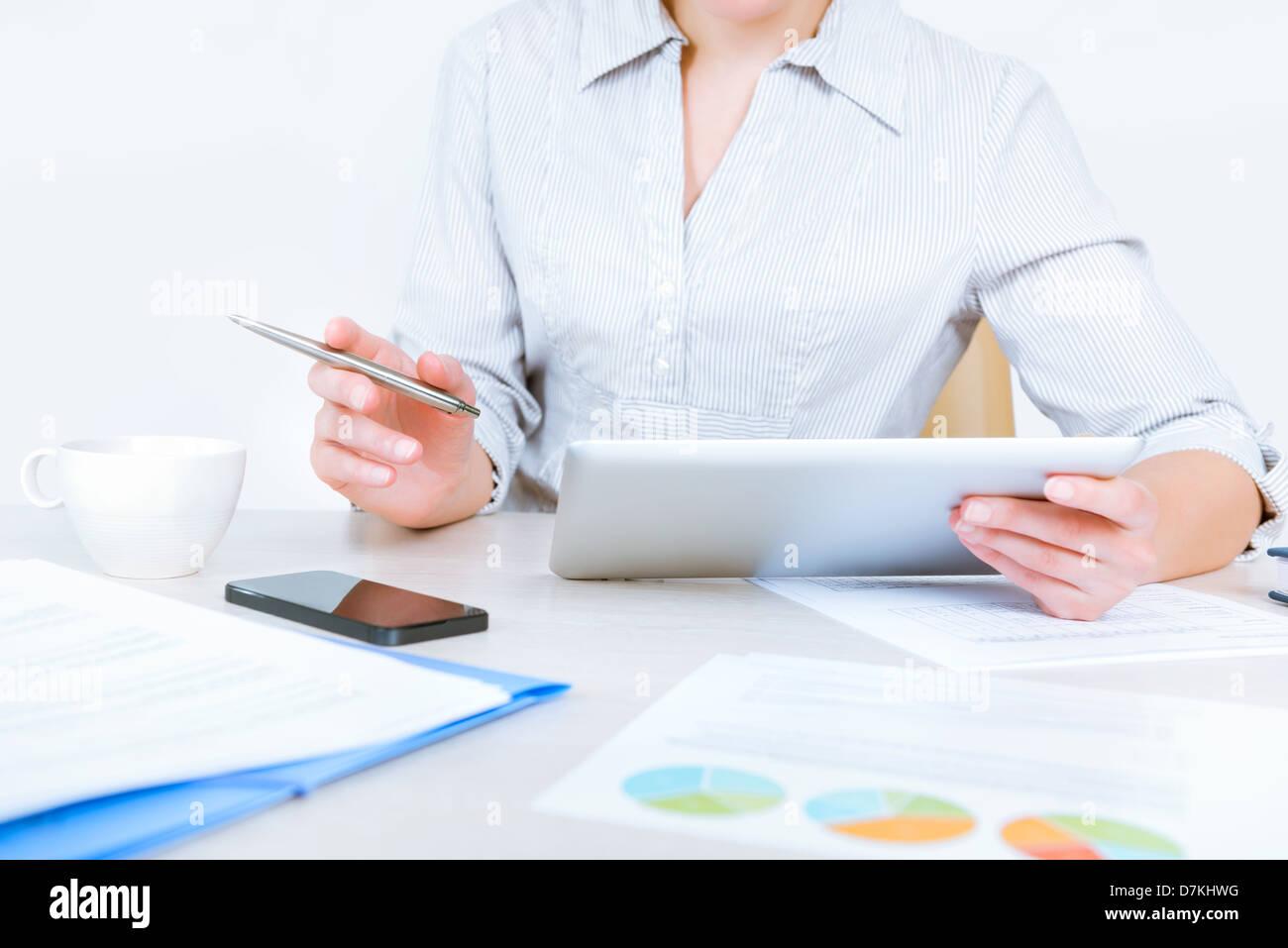 Chemise décontractée détendue woman sitting at desk et de travailler avec des données sur digital tablet dans le Banque D'Images