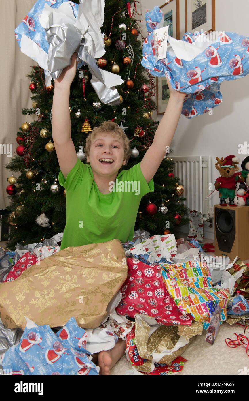 Jeune garçon et papier d'emballage le jour de Noël Photo Stock