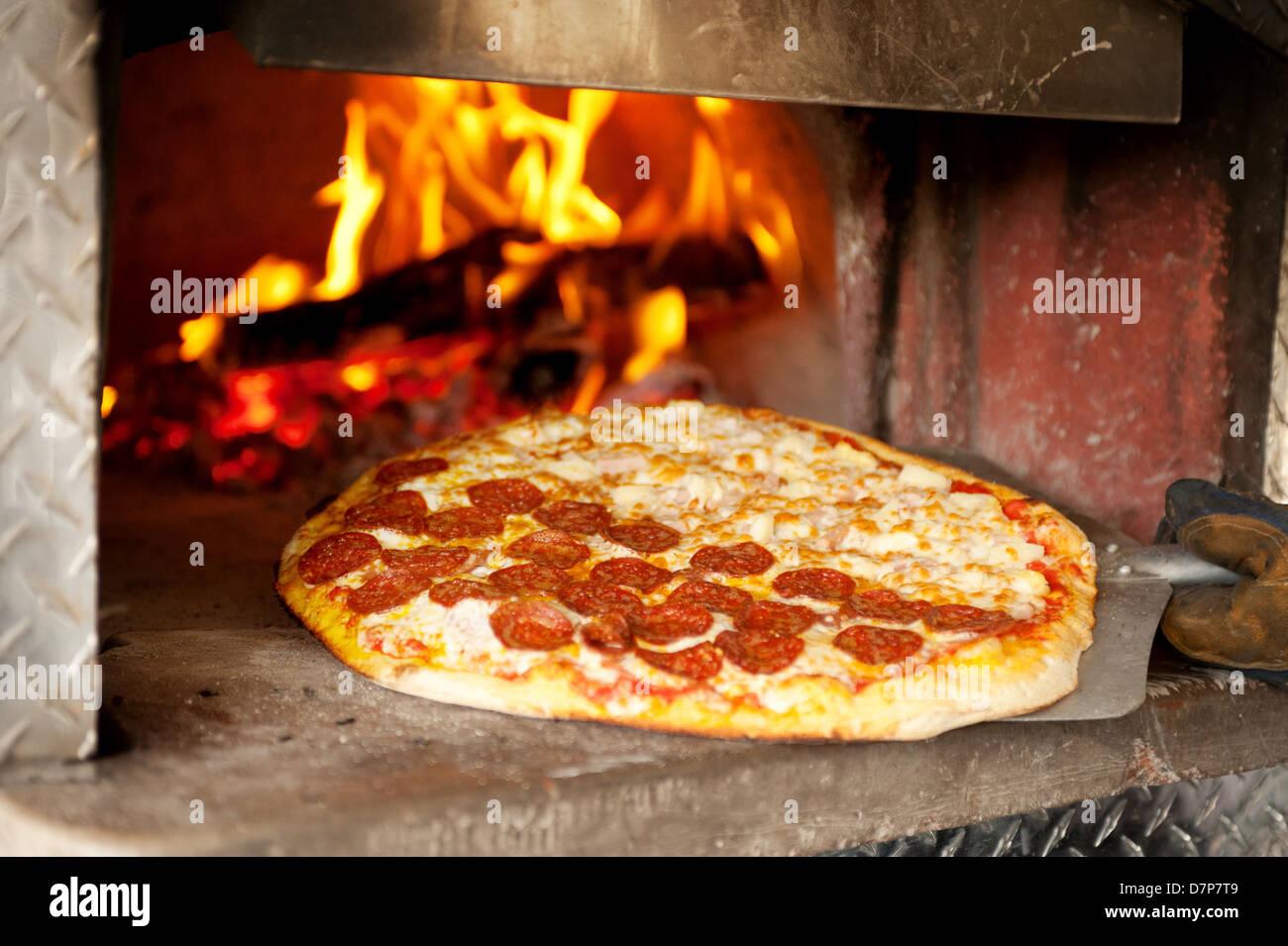 Une pizza au pepperoni, cuit dans un four à pizza au feu de bois. Photo Stock