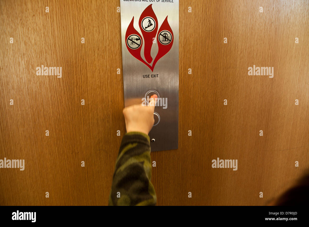 La main de l'enfant en poussant le bouton d'appel d'ascenseur - USA Photo Stock