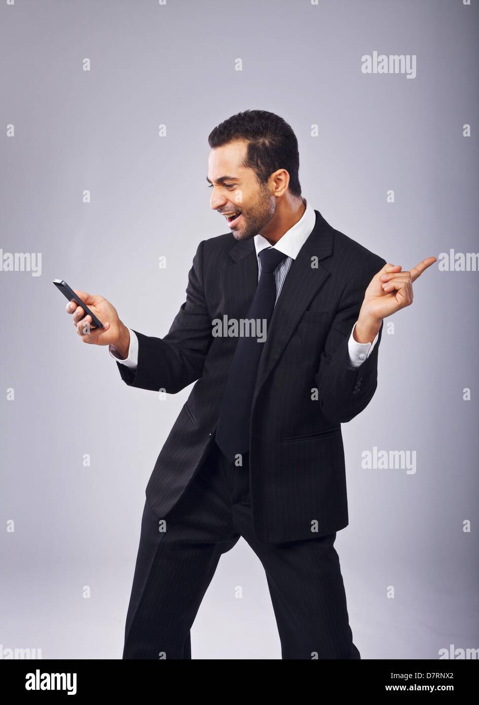 Young businessman with phone danser hors de la joie Photo Stock