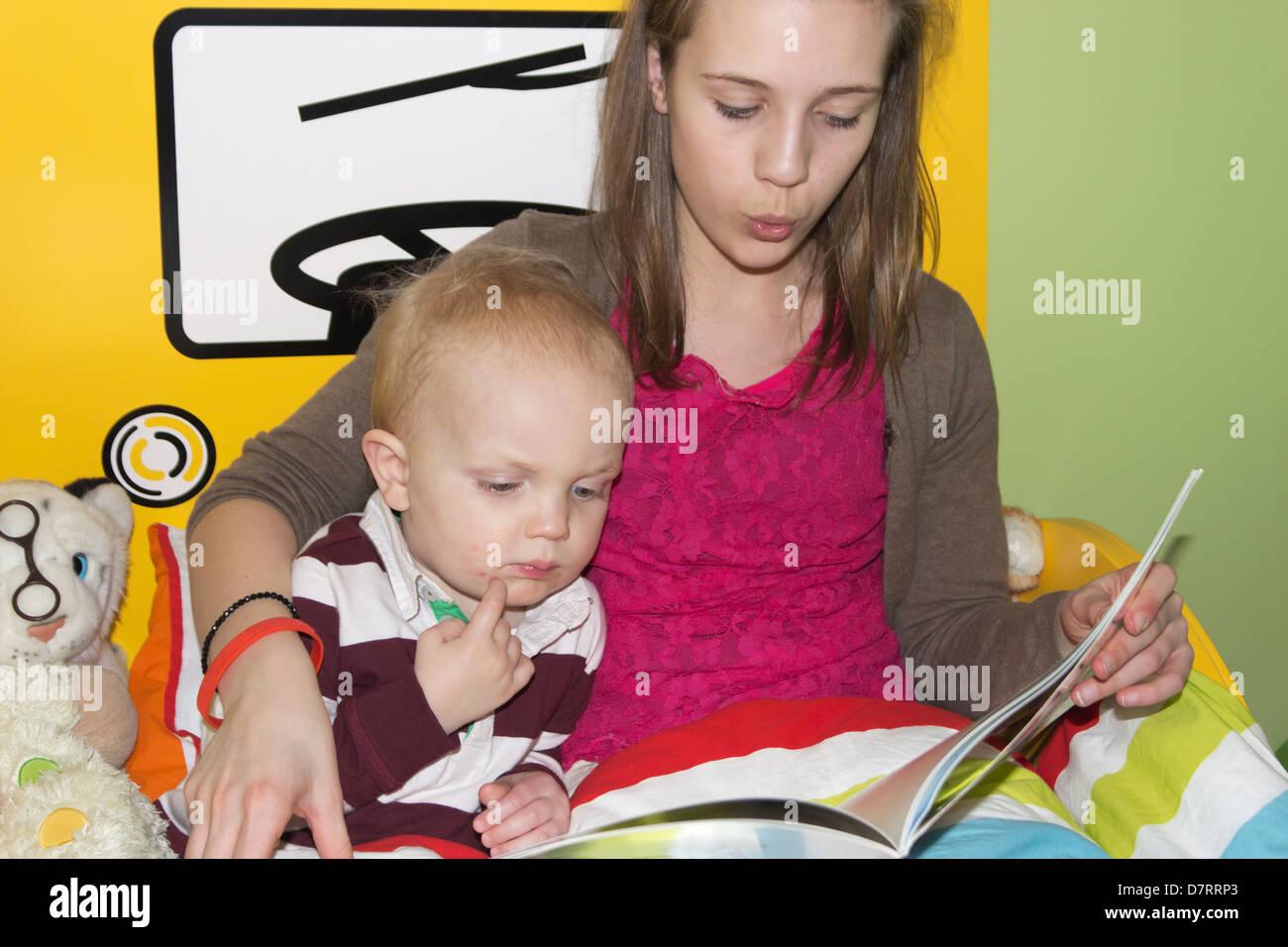 Jeune fille lisant une histoire à un petit garçon. Banque D'Images