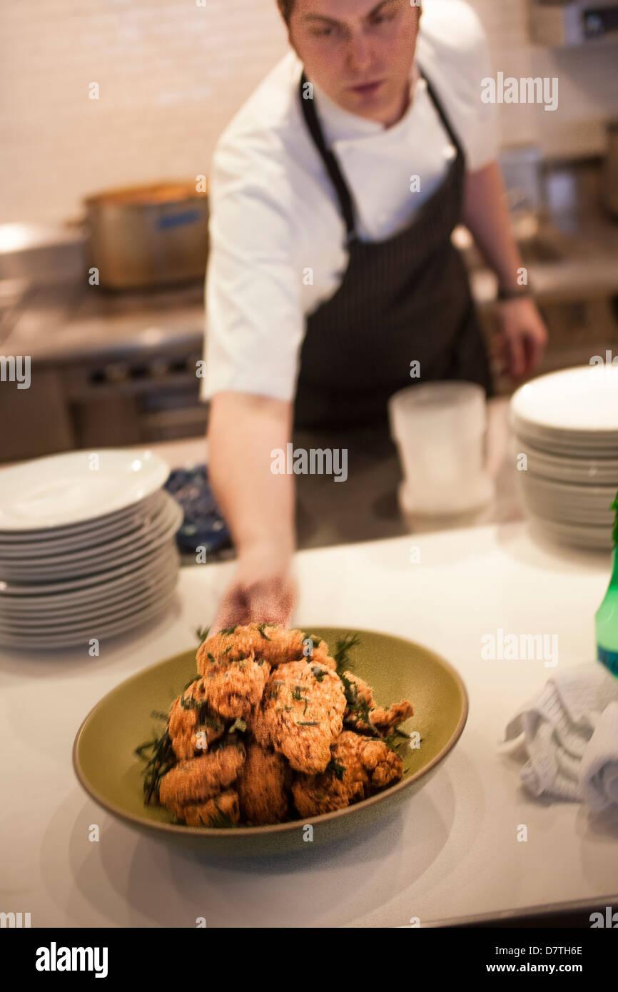 Chef holding seau de golden fried chicken Photo Stock