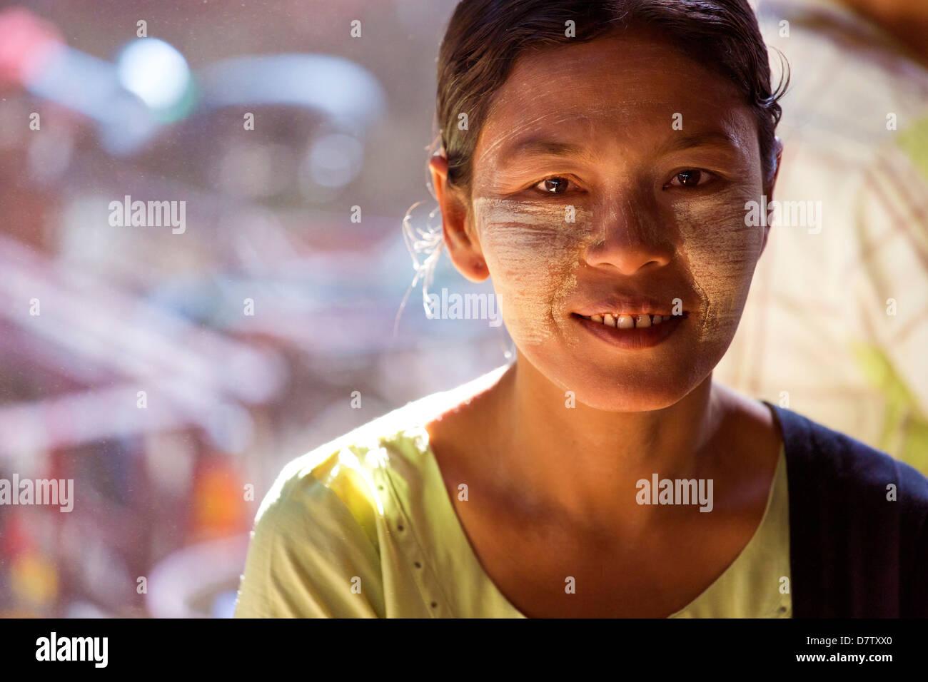 Femme avec Thanakha visage traditionnel peinture, Thiri Mingalar, marché de Yangon (Rangoon), la Birmanie Photo Stock