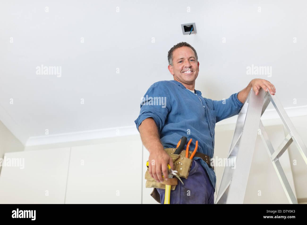 L'homme travaillant sur plafond lumineux Photo Stock