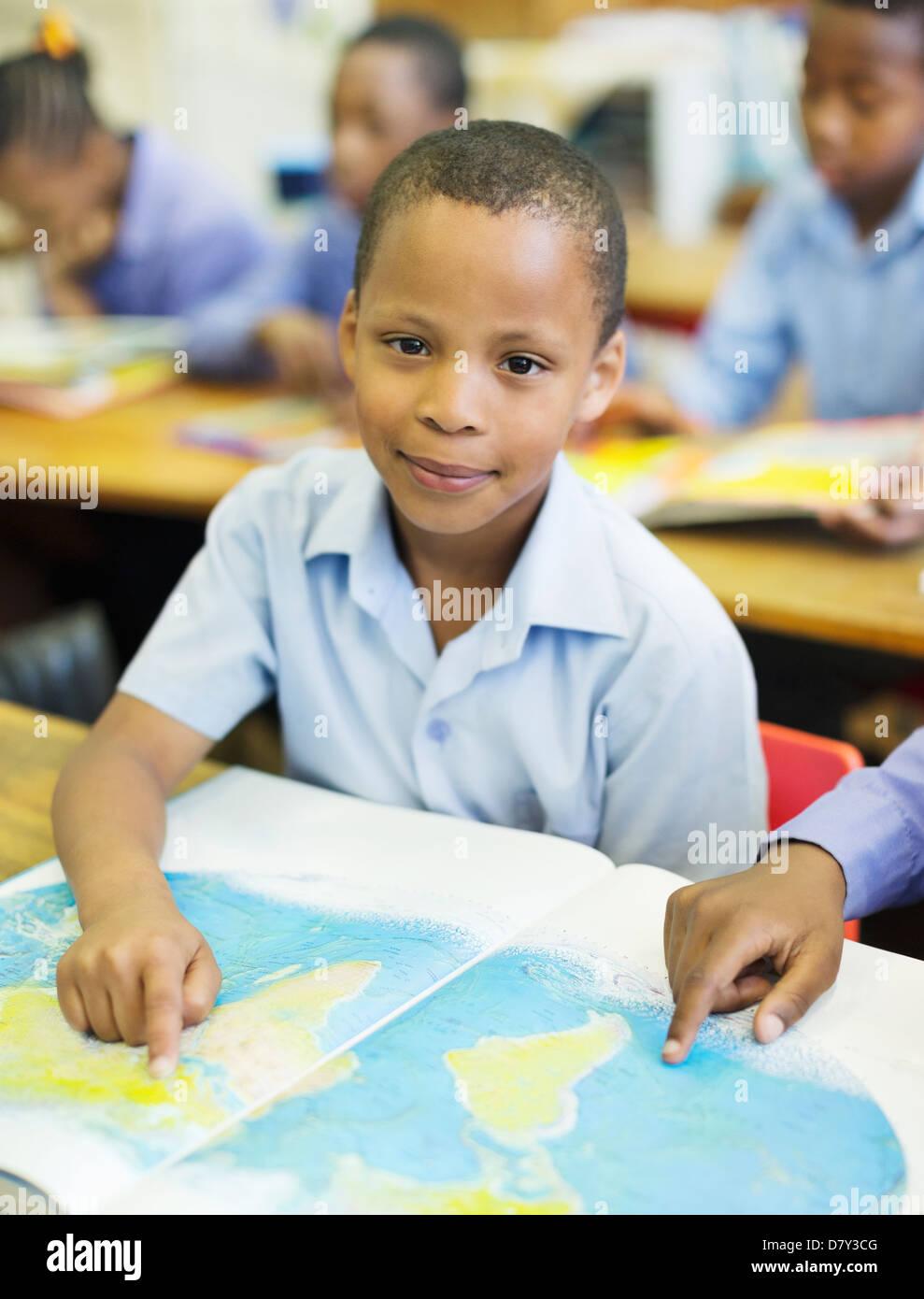 Les élèves à l'aide de la carte du monde en classe Photo Stock