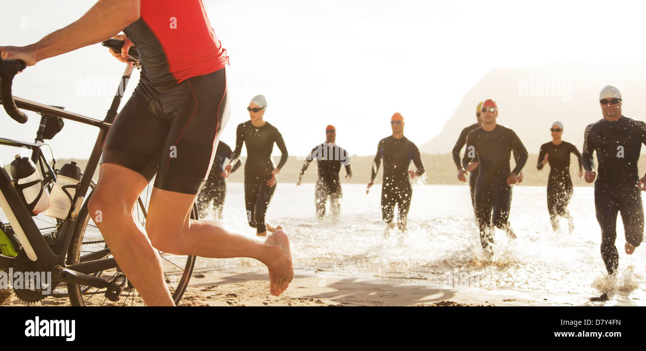 Triathletes emerging from water Photo Stock