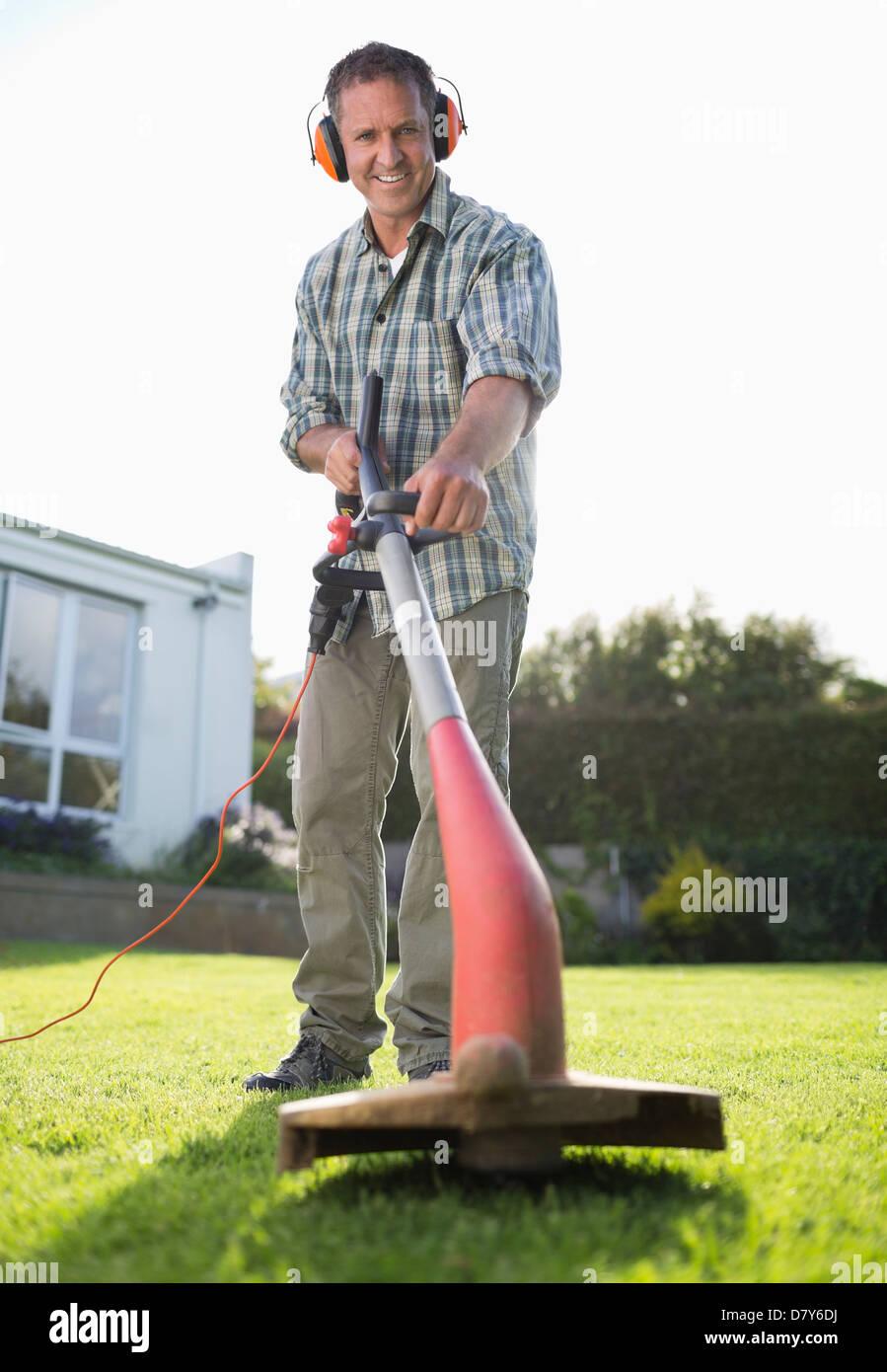 À l'aide de l'homme lutte contre les mauvaises herbes dans la cour whacker Photo Stock