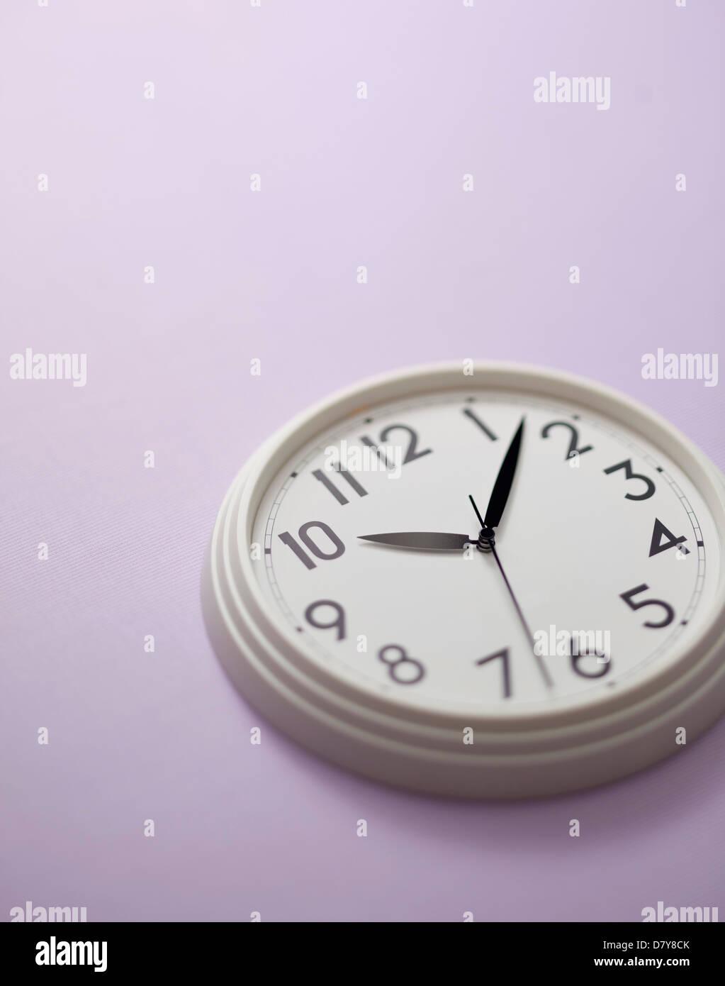 Une petite horloge murale sur un mur violet clair. Photo Stock
