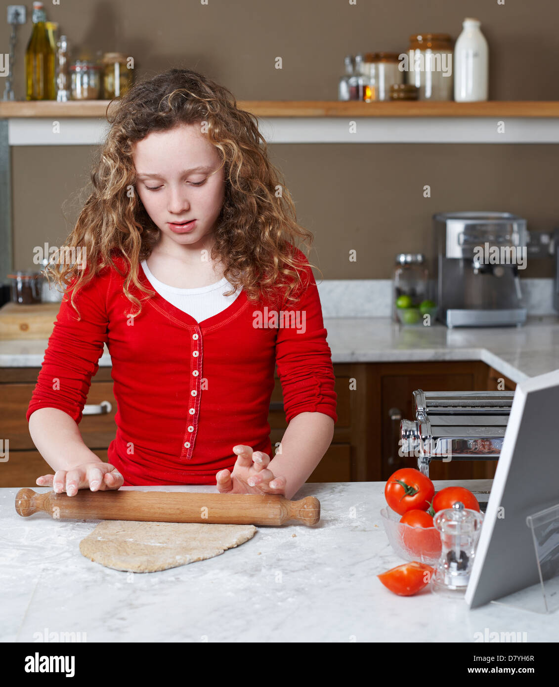 Girl pâte de roulement dans la cuisine Photo Stock