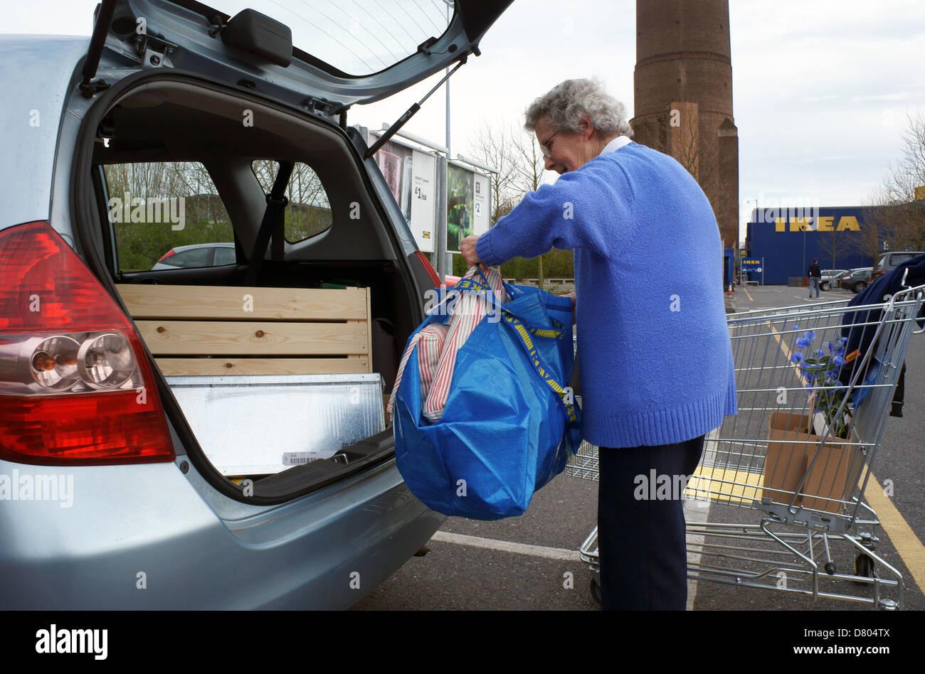 Pensionné féminine senior citizen achats chargement de ikea Croydon à l'arrière d'une Photo Stock