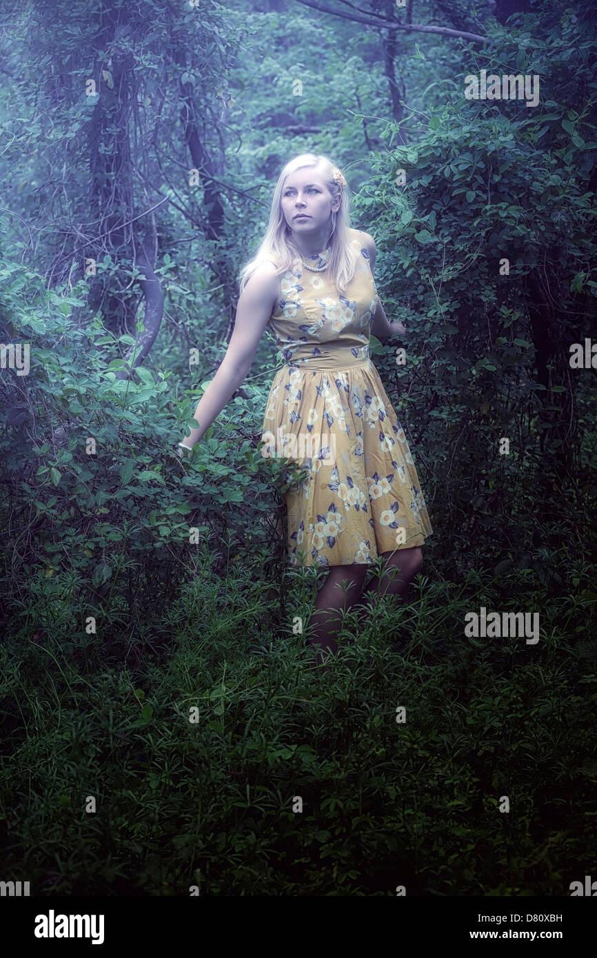 Une fille blonde avec une robe jaune dans les bois Banque D'Images