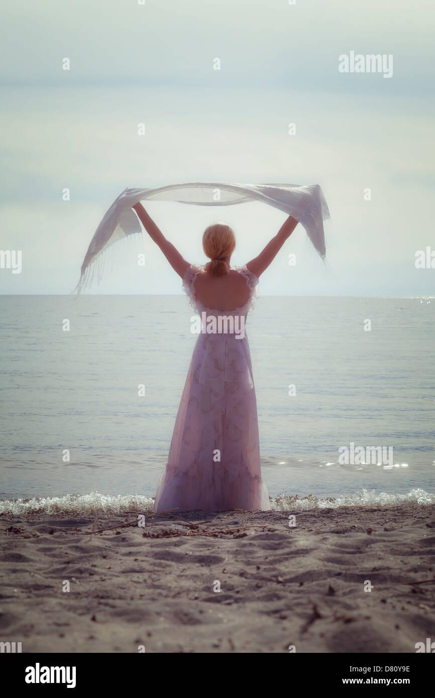 Une femme à la plage avec un châle blanc Photo Stock