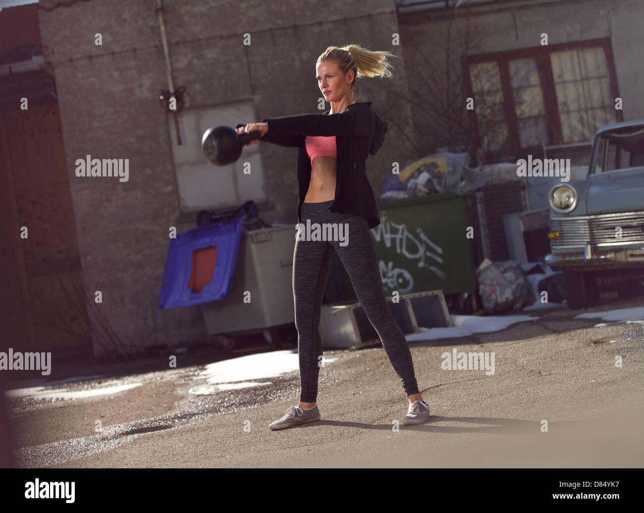Jeune femme fitness kettlebell balançant le crossfit au cours de la formation Photo Stock