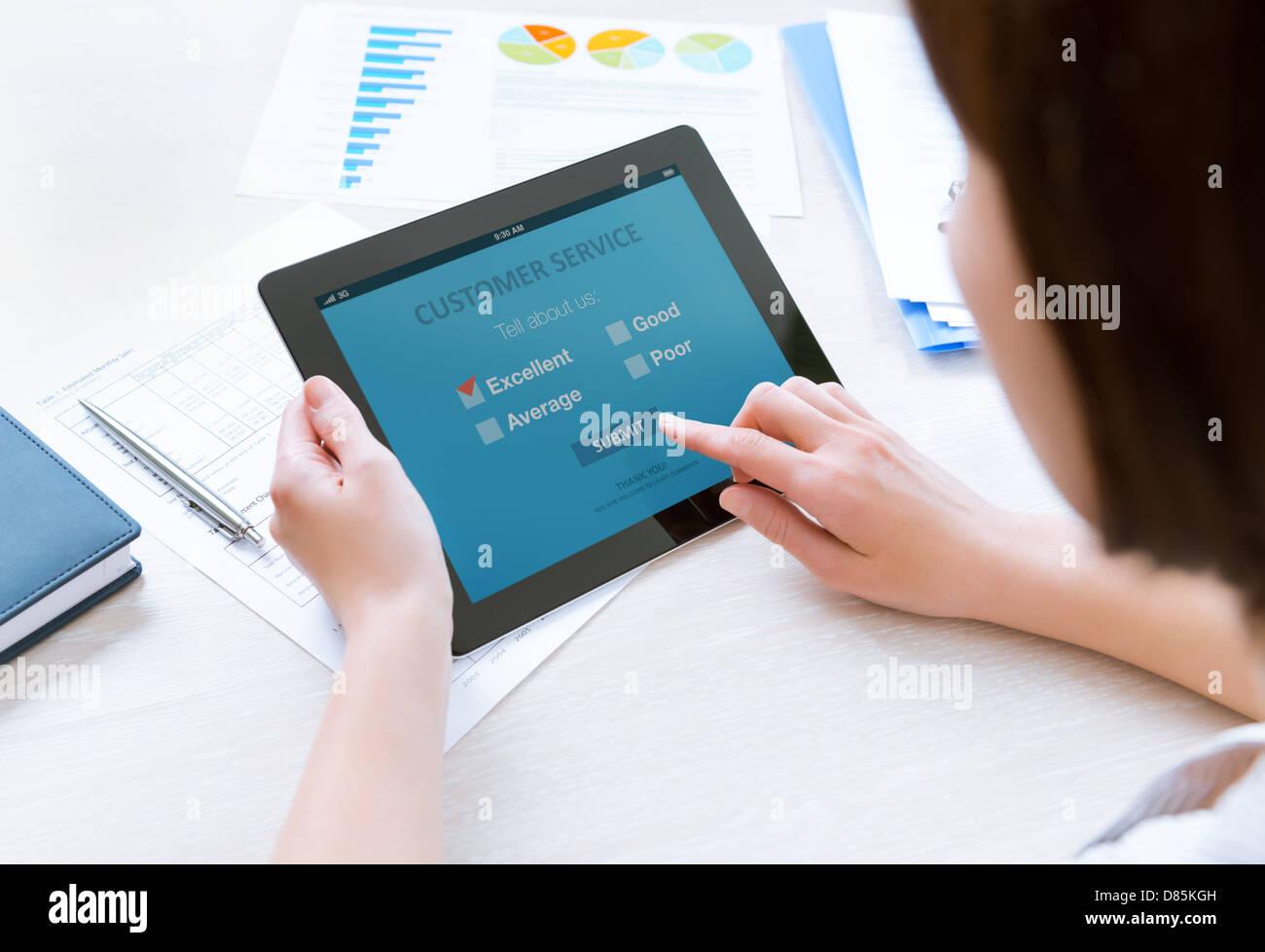Businesswoman holding digital tablet moderne avec service clientèle Formulaire d'enquête sur un écran. Photo Stock