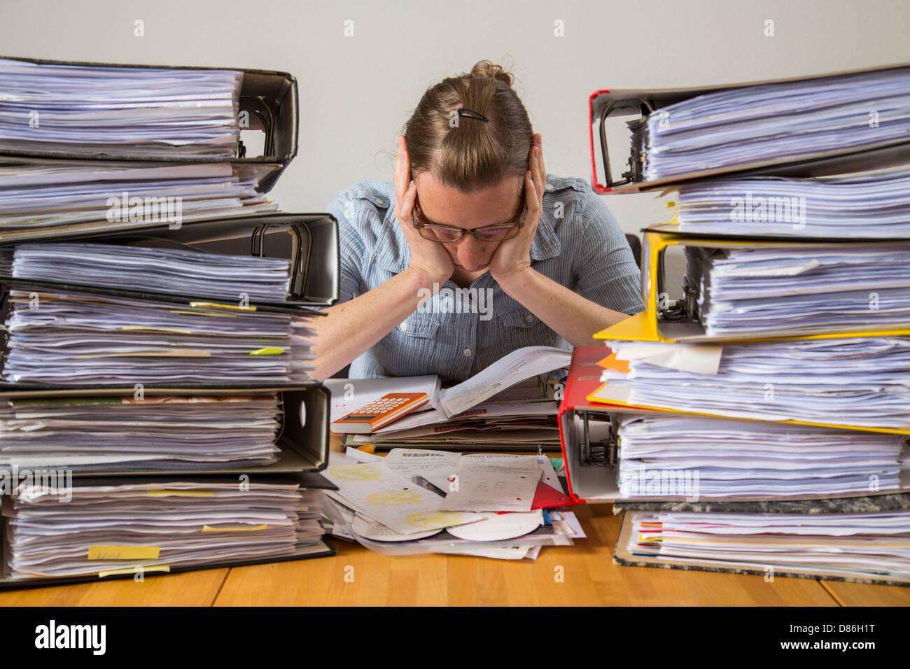 Jeune femme est à la maison et régler les factures, reçus et autres documents pour sa déclaration Photo Stock