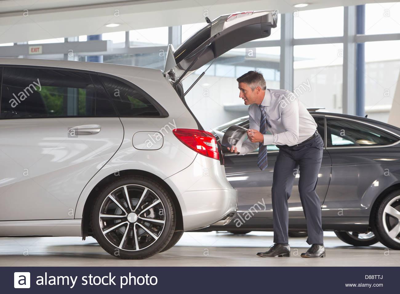 Avec l'homme à la brochure de berline en voiture en car dealership showroom Photo Stock