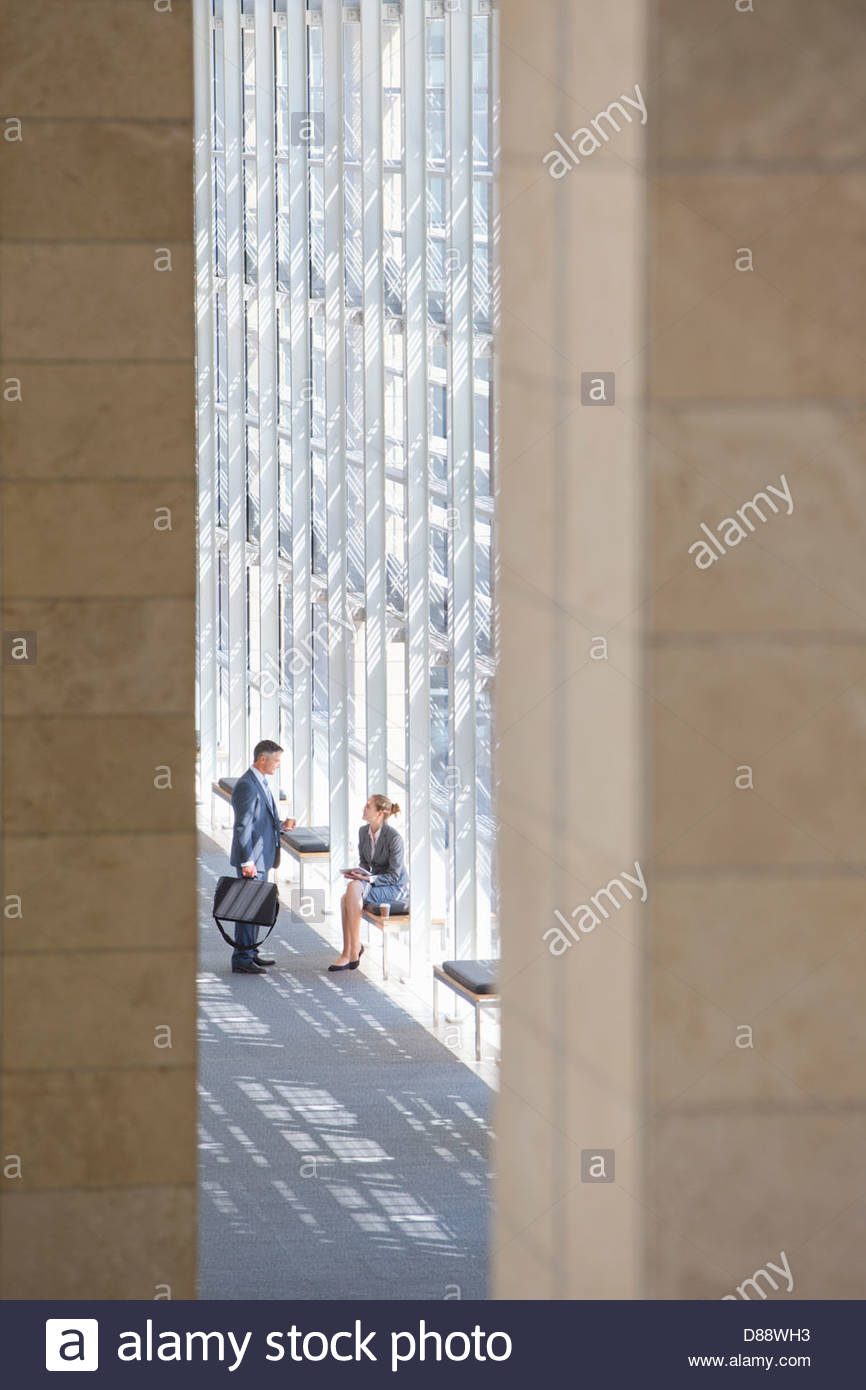 Businessman and businesswoman talking in lobby of modern office Banque D'Images