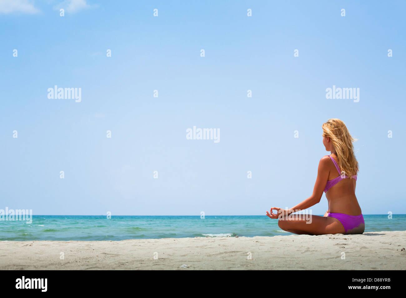 Le yoga en journée ensoleillée sur la plage Photo Stock