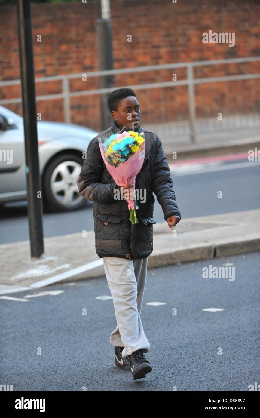 Woolwich, Londres, Royaume-Uni. 23 mai 2013. Un jeune garçon porte les fleurs à laisser sur les grilles près du lieu du meurtre. Les fleurs sont laissés par les bienfaiteurs le long des rampes près de l'endroit où le batteur Lee Rigby du 2e Bataillon du Régiment royal de fusiliers a été tué hier à l'extérieur des casernes de Woolwich. Crédit: Matthieu Chattle/Alamy Live News Banque D'Images