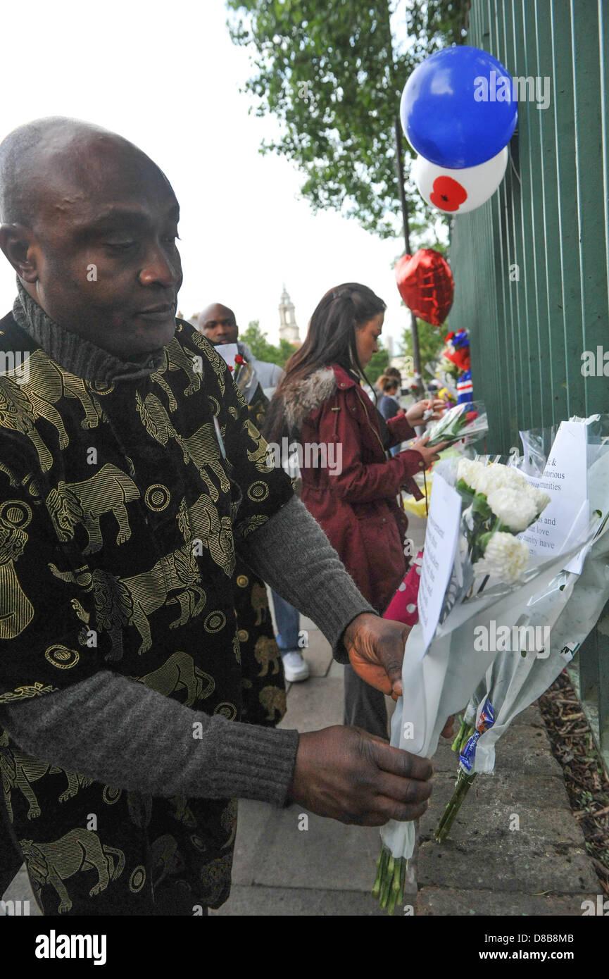 Woolwich, Londres, Royaume-Uni. 23 mai 2013. Un groupe de Nigérians de Shepherds Circulation laisser fleurs sur les grilles sur les lieux du crime à Woolwich. Les fleurs sont laissés par les bienfaiteurs le long des rampes près de l'endroit où le batteur Lee Rigby du 2e Bataillon du Régiment royal de fusiliers a été tué hier à l'extérieur des casernes de Woolwich. Crédit: Matthieu Chattle/Alamy Live News Banque D'Images