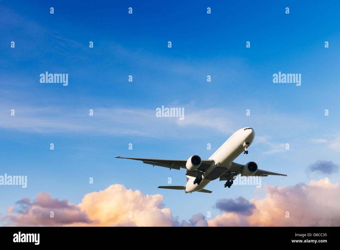 Avion - Boeing 777 en venant à la terre au coucher du soleil. Photo Stock