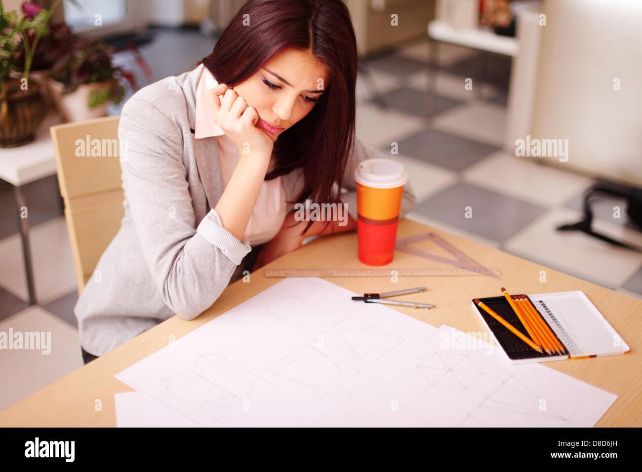 Jeune architecte pensif un problème avec ses dessins techniques Photo Stock