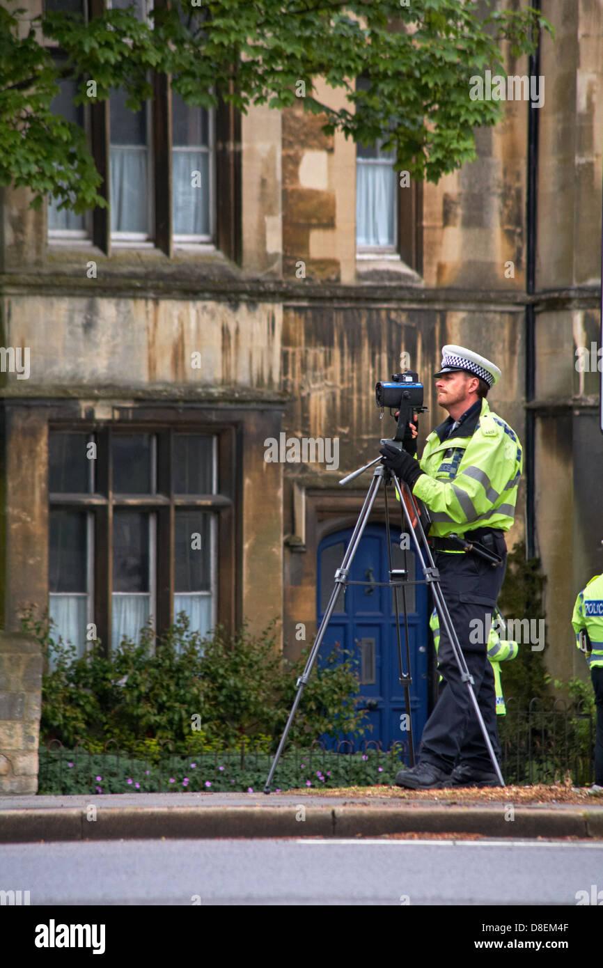 Agent de police de trafic mobile avec appareil photo sur trépied, contrôle de vitesse en accélérant Photo Stock