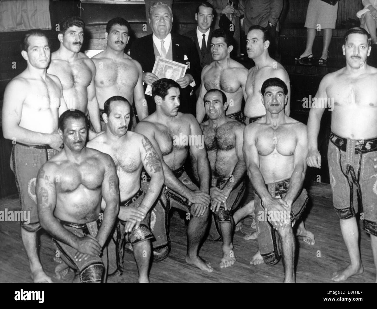 Avocat et homme politique Carlo Schmid (m, arrière) visite une école de sport à Téhéran (Iran) en octobre 1964 et est entouré par des hommes musclés. Banque D'Images