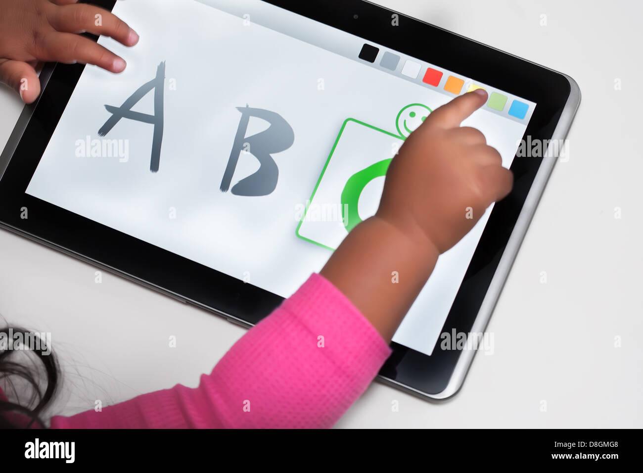 La main d'un enfant sur un écran tactile Tablet avec des logiciels éducatifs. Photo Stock
