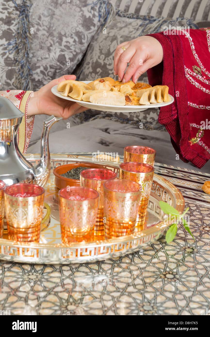 Mains d\u0027une femme marocaine ramadan présentant des gâteaux et du thé à un  invité