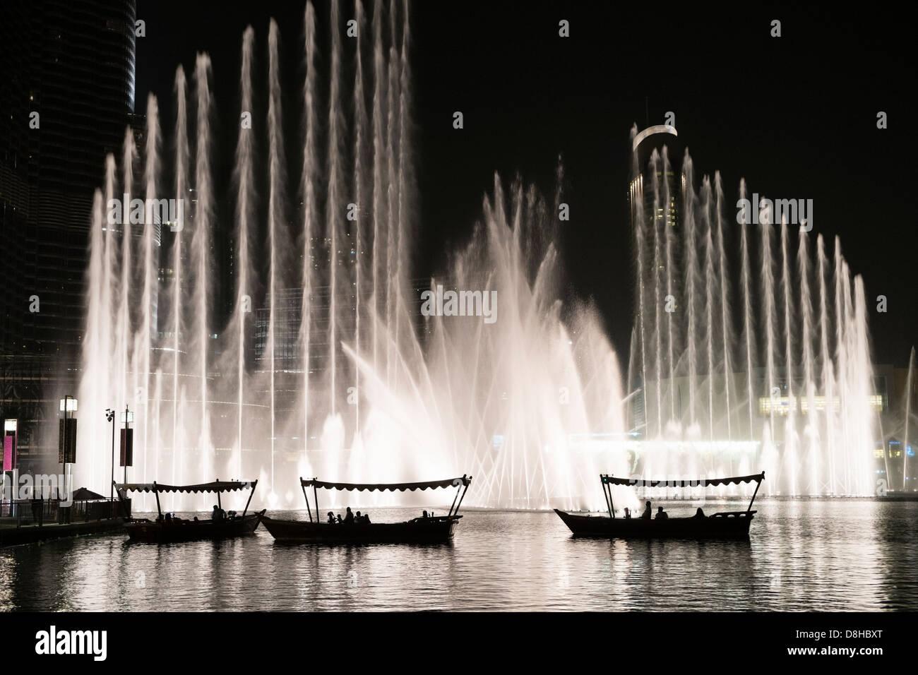 De petites embarcations transportant les touristes à regarder la fontaine de Dubaï au centre commercial Photo Stock