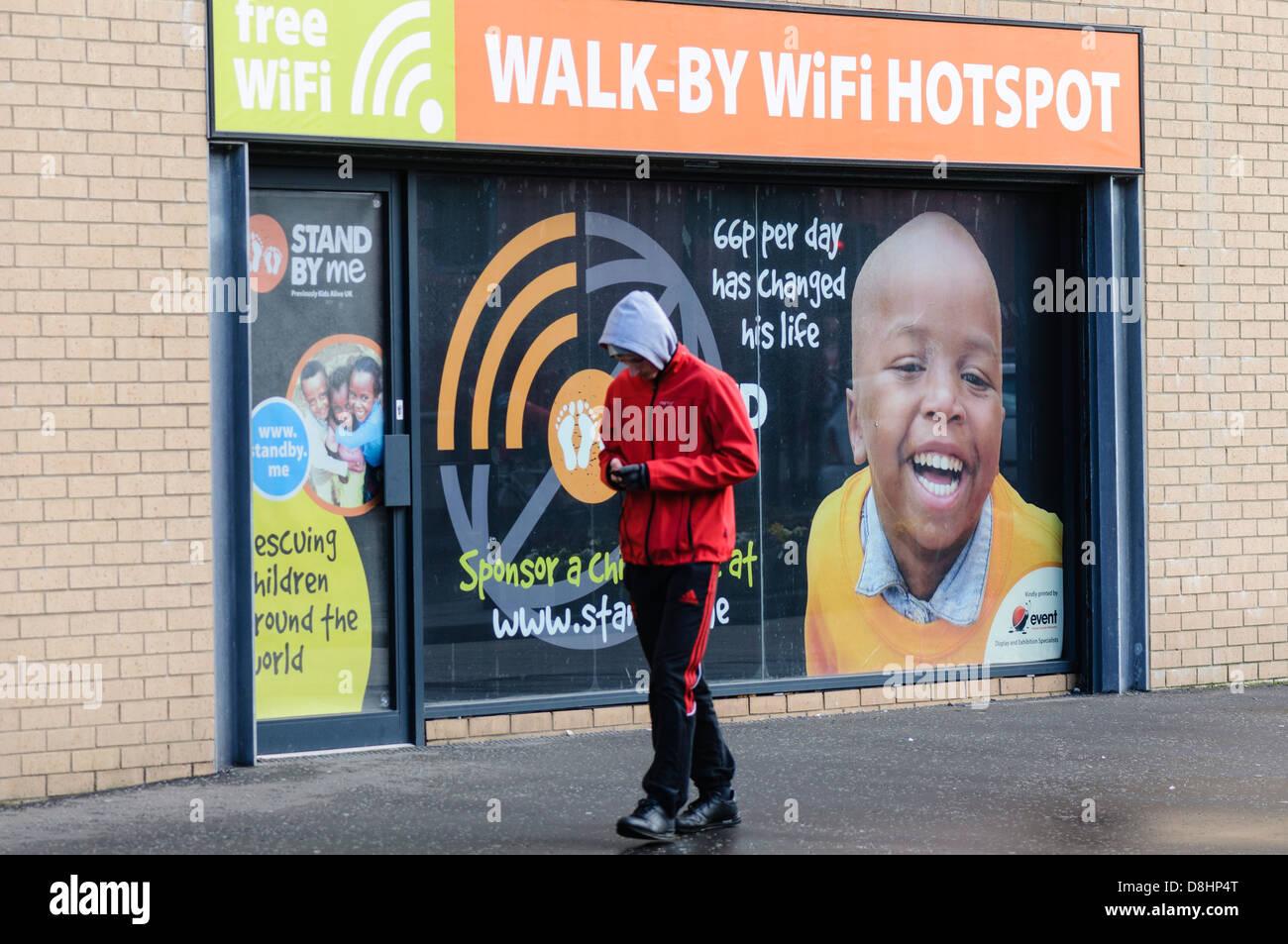 Adolescent marche dernières une par hotspot Wifi tout en utilisant son smartphone Photo Stock