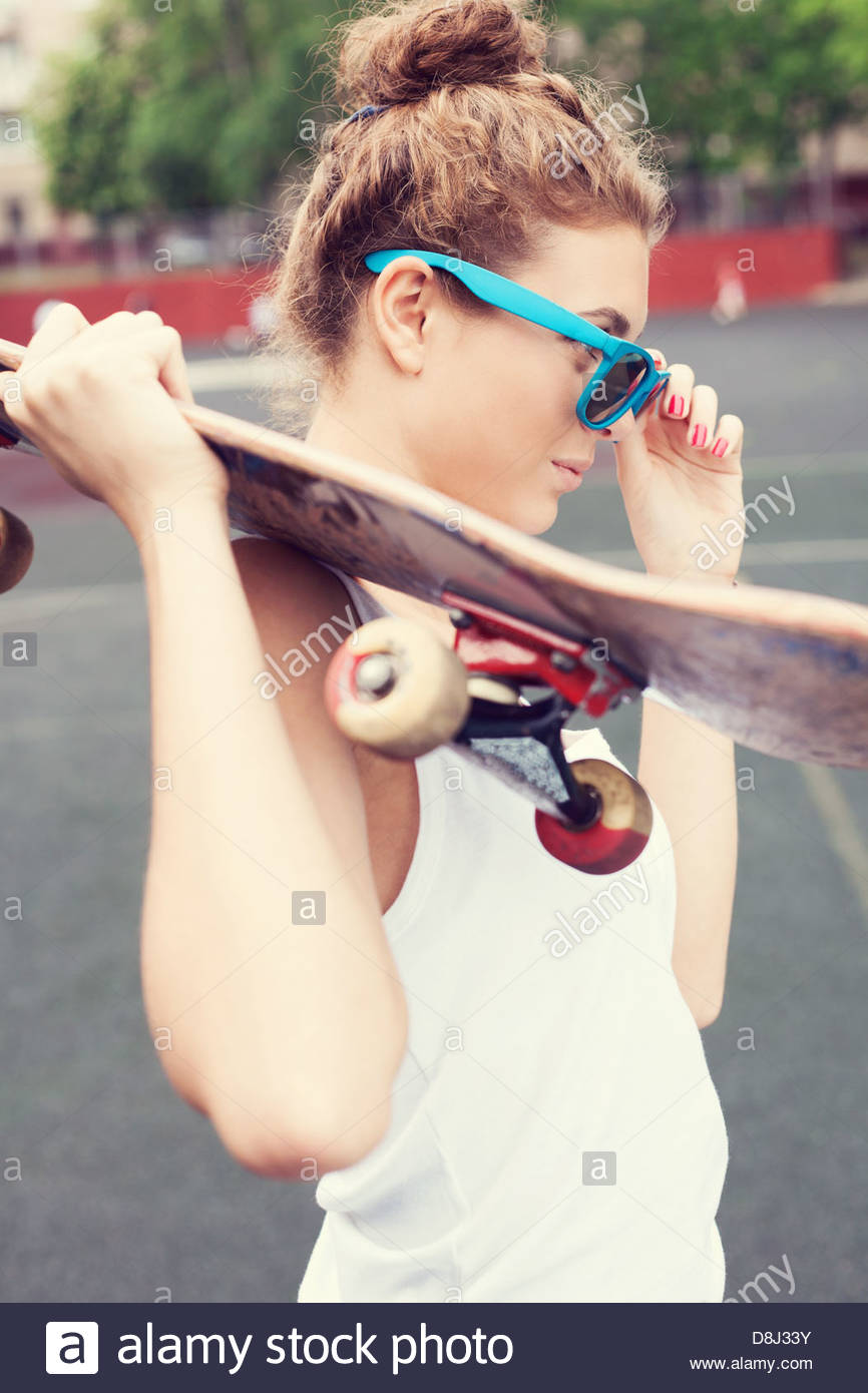 Jeune femme en bleu biautiful lunettes debout sur le terrain de jeu avec un skateboard dans ses mains dans la journée. Banque D'Images