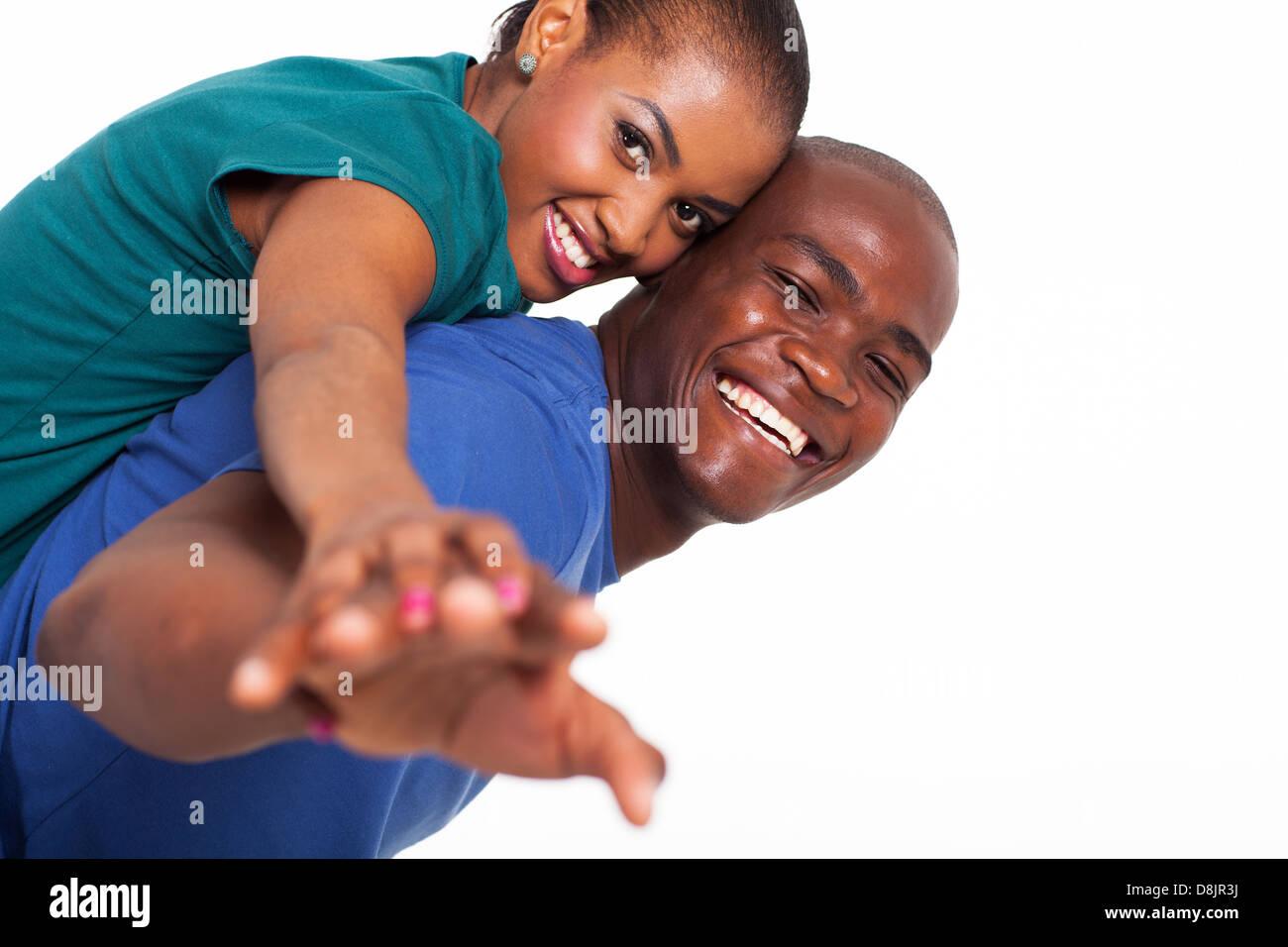 Happy young African woman piggyback ride on boyfriends back avec leurs mains tendues Photo Stock