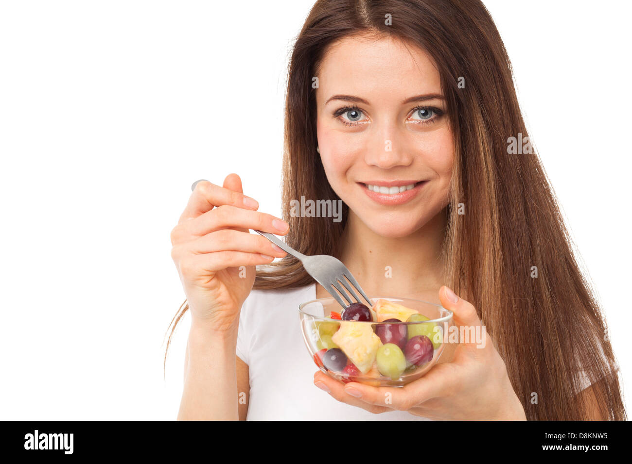 Close up portrait of a nice woman eating fruits, isolated on white Photo Stock